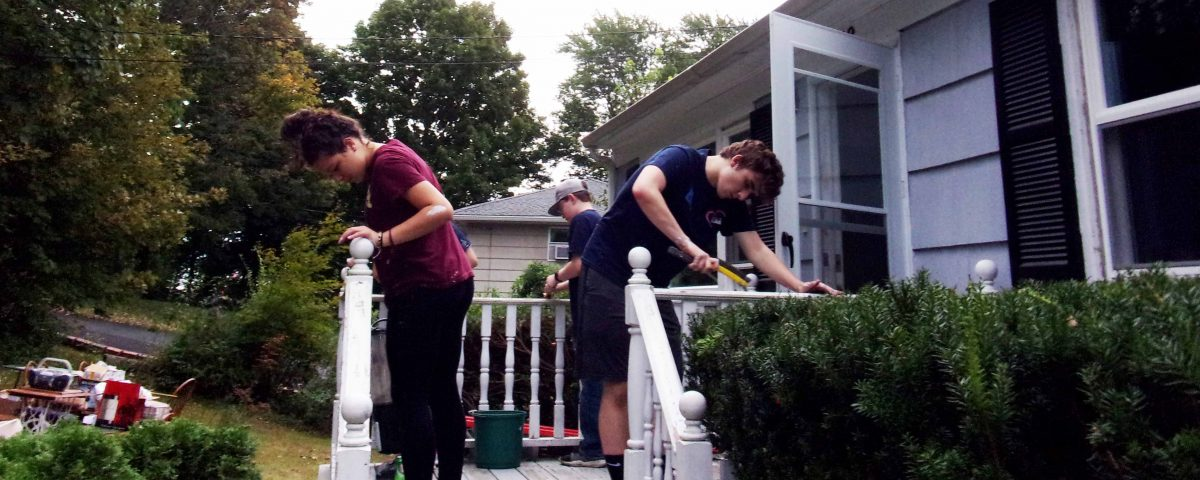 Volunteers Ana Pesarini, Jack Reynolds and Ryan Nason repair the front porch at the Finnegan's home on Saturday, September 22nd.